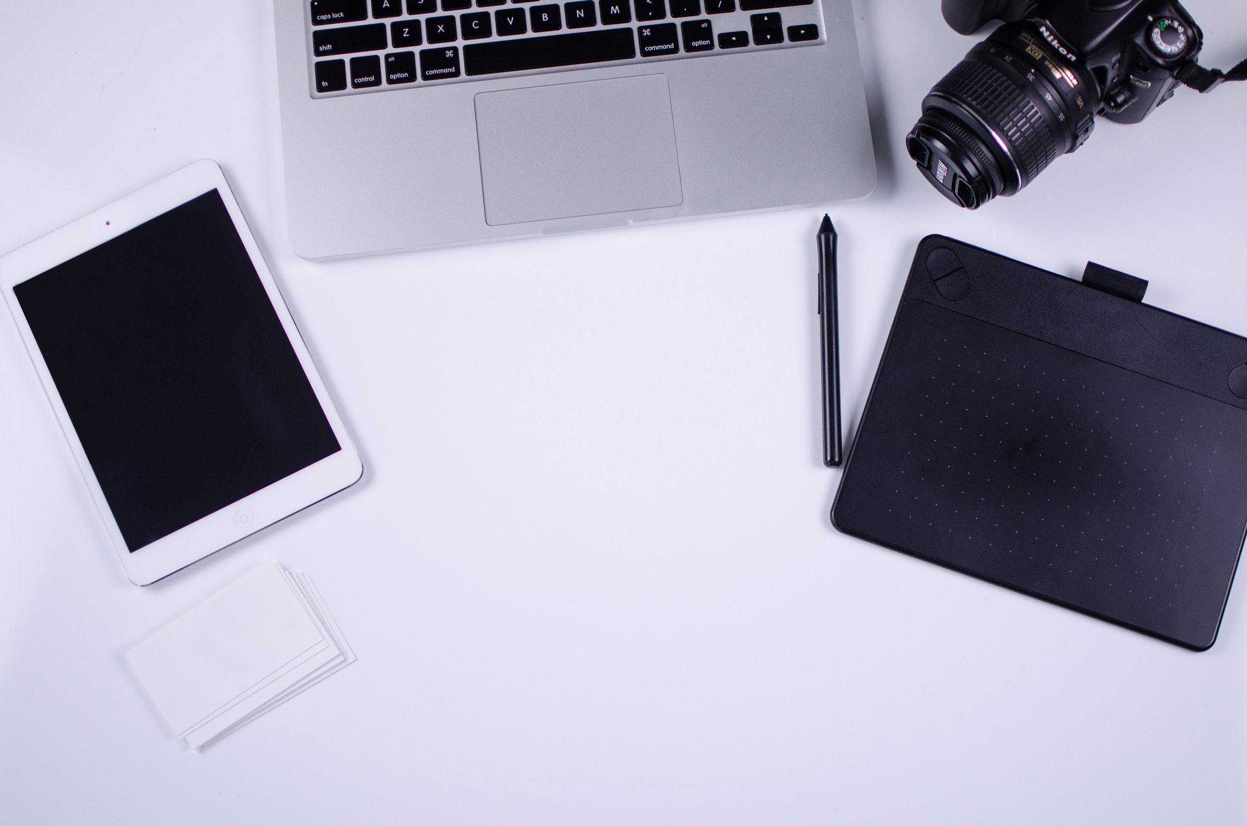 a tablet, laptop, camera, and notebook arranged on a desk
